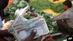 Người bán rau quả trong chợ bán sĩ của Ấn Độ đếm những đồng rupee vừa thu được