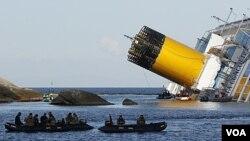 Para penyelam bersiap di dekat kapal Costa Concordia (24/1). Sejauh ini 16 jenazah korban kapal pesiar sudah ditemukan.