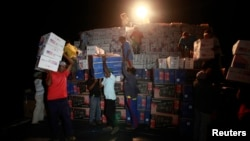 Wayuu Indians carry boxes of goods from a cargo ship docked at a port in Pueblo Nuevo, Colombia, August 15, 2012.