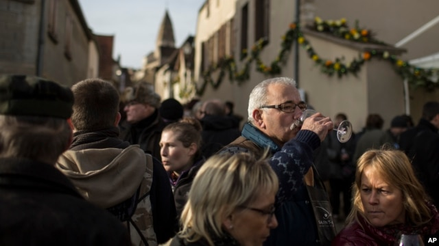 FILE - People taste wine during an annual rite known as the Saint Vincent Tournante, in Saint-Aubin, central France, January 2014.