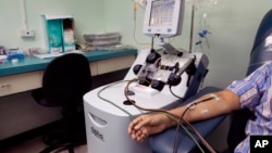 A recovered COVID-19 patient donates blood at the Arnulfo Arias Madrid Hospital, in Panama City, Wednesday, May 13, 2020. The blood product donated from recovered COVID-19 patients, known as convalescent plasma, may have antibodies that can help those cri