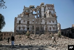 FILE - Houthi Shi'ite rebels walk amid the rubble of the Republican Palace that was destroyed by Saudi-led airstrikes, in Sana'a, Yemen, Dec. 6, 2017.