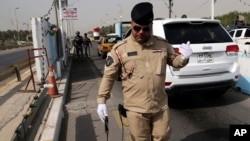 Cảnh sát Iraq sử dụng thiết bị dò bom tại 1 trạm kiểm soát ở Baghdad, Iraq, 11/10/2014.