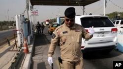 Cảnh sát liên bang Iraq cầm thiết bị phát hiện bom tại một chốt kiểm soát ở Baghdad, ngày 11/10/2014.