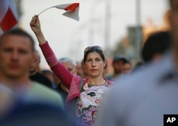 """A Belarusian protester waves an opposition flag during a rally after parliamentary election in Minsk, Belarus, Sept. 12, 2016. About 150 Belarusian opposition activists gathered for an unauthorized rally under the slogan """"We demand real elections."""""""