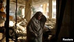 2014年7月17日,一名巴勒斯坦妇女在加沙城自家房内瓦砾旁,警方说这间房屋成为以色列空袭的目标。