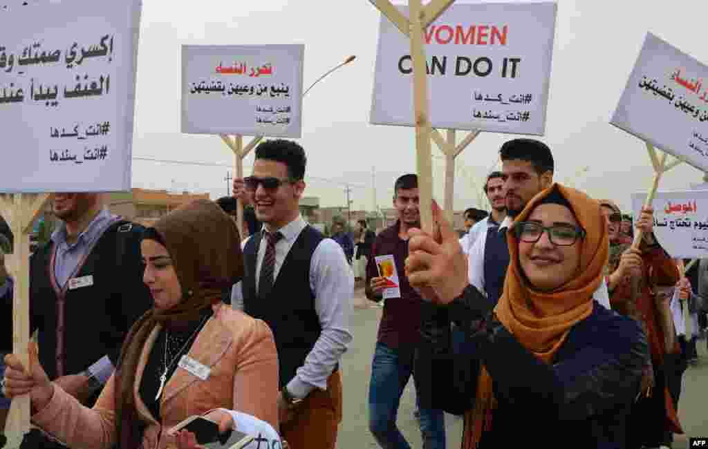Des jeunes irakiennes participent à la marche de la Journée des droits des femmes dans l'ancienne ville de Mossoul, le 8 mars 2018.