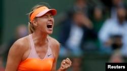 Maria Sharapova dari Rusia bereaksi setelah mengalahkan Garbine Muguruza dari Spanyol dalam perempat final Perancis Terbuka di stadion Roland Garros di Paris (3/6). (Reuters/Gonzalo Fuentes)
