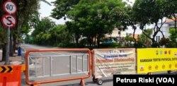 Jalan Raya Darmo di Surabaya ditutup untuk mengurangi mobilitas warga dan kendaraan di jalan itu, 4 April 2020. (Foto: Petrus Riski/VOA)