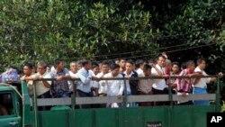 Para tahanan Myanmar naik truk saat dibebaskan dari penjara Insein, 2014.
