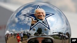 Dallas Cowboys fan Gregg Wilson, of Dallas, arrives for the Pro Football Hall of Fame inductions, including that of Cowboys owner Jerry Jones, whose photo is on the helmet, at the Pro Football Hall of Fame on Saturday, Aug. 5, 2017, in Canton, Ohio.