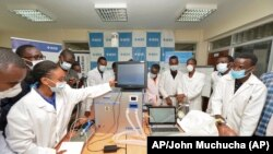 In this photo taken Monday, April 13, 2020, medical students test a self-designed computer-controlled ventilator prototype at the Chandaria Business and Incubation Centre of Kenyatta University in Nairobi, Kenya. (AP PHOTO/John Muchucha)