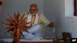 Perdana Menteri India Narendra Modi mencoba tangannya di roda berputar saat berkunjung ke Gandhi Ashram, kediaman Mahatma Gandhi, di Ahmadabad, India, 29 Juni 2017.