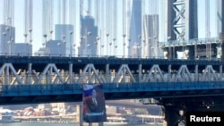 A banner with an image of Russian President Vladimir Putin hangs from the Manhattan Bridge in New York City, Oct. 6, 2016.