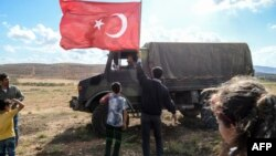 FILE - A man waves a Turkish national flag as a Turkish army vehicle drives past during a demonstration in support of the Turkish army's operation near the Turkey-Syria border near Reyhanli, Hatay, Oct. 10, 2017.