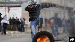 Para demonstran Palestina melempar batu ke arah pos tentara Israel dan membakar ban-ban dalam aksi protes di luar penjara Israel di Tepi Barat (19/2).