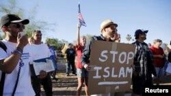 """Namoyishchi qo'lidagi plakatda """"Islomni to'xtating"""" deb yozilgan, Arizona, 29-may, 2015-yil."""