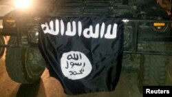 FILE - The Islamic State flag is displayed during celebrations in Mosul, Iraq.