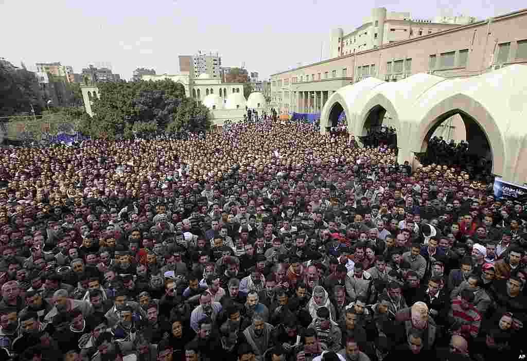 Thousands of Egyptian Christians watch on a giant screen the funeral of Pope Shenouda oustide St. Mark Coptic Orthodox Church in Cairo. (AP)