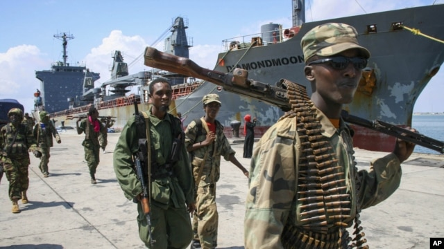 Somali National Army soldiers and pro-government Ras Kamboni brigadiers walk along seaport quay, Kismayo, Nov. 2, 2012.