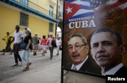 Tourists pass by images of U.S. President Barack Obama and Cuban President