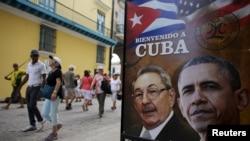 អ្នកទេសចរដើរកាត់រូបប្រធានាធិបតីអាមេរិកលោកបារ៉ាក់ អូបាម៉ា និងប្រធានាធិបតីគុយបាលោក Raul Castro នៅក្នុងបដាមួយដែលប្រែថា «ស្វាគមន៍មកកាន់គុយបា» នៅមាត់ទ្វារភោជនីយដ្ឋានមួយក្នុងក្រុងឡាហាវ៉ាន នាថ្ងៃទី១៧ ខែមិនា ឆ្នាំ២០១៦។