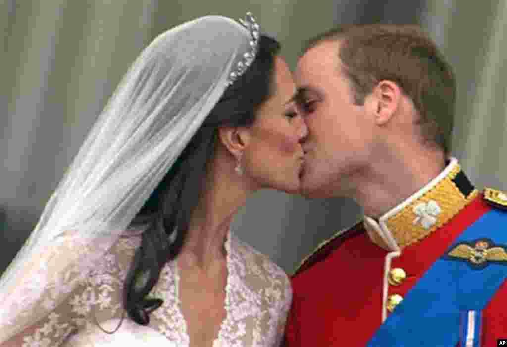 Може да ја бакнете сопругата! Принцот Вилијам и новоименуваната војвотка Кејт од Кембриџ на балконот на Бакингамската палата. (AP Photo/APTN)