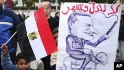Egyptian children hold an anti-Mubarak cartoon during a protest in Alexandria, Egypt, February 4, 2011