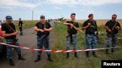 Separatistas prorrusos armados montan guardia en el sitio en que cayó el avión MH17.