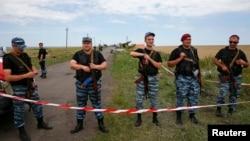 Dân quân vũ trang thân Nga đứng gác tại địa điểm nơi máy bay Malaysia bị bắn rơi gần làng Hrabove, khu vực Donetsk, ngày 20/7/2014.
