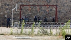 FILE - In this Oct. 8, 2014, photo, police officers take positions by nooses prepared to execute men at a jail in Kabul, Afghanistan. Afghanistan has recently hanged six men convicted of terrorism, signaling a tougher approach toward the Taliban.