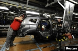 FILE - Nissan technicians work on a Qashqai car on the production line at the company's plant in Sunderland, Britain, Nov. 9, 2011.