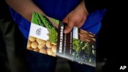 一位中國訪客在上海國際大豆展上手握一家美國大豆公司的傳單。(2018年4月12日)
