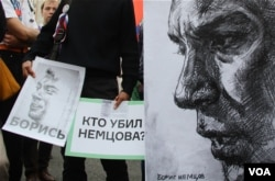 FILE - Anti-government protesters hold posters asking who killed opposition leader Boris Nemtsov as they march during an opposition rally in Moscow, Russia, Sept. 20, 2015. (Photo by M. Eckels)