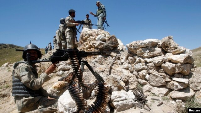 FILE - Afghan border policemen take their positions at the Goshta district of Nangarhar province border, where Afghanistan shares borders with Pakistan.