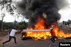 Demonstrators throw wood onto burning tires at a barricade during a protest as Honduran President Juan Orlando Hernandez is sworn in for a new term in Tegucigalpa, Honduras, Jan. 27, 2018.