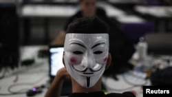 "A man wearing a Guy Fawkes mask surfs the web during a ""Campus Party"", an annual week-long, 24-hour technology festival that gathers around 8000 hackers, developers, gamers and computer geeks from around the world in Sao Paulo, January 30, 2013."