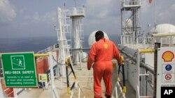 Seorang pekerja perusahaan Shell berada di atas kapal minyak di lepas pantai Nigeria (foto: dok). DPR Nigeria meluncurkan penyelidikan terhadap skandal penipuan industri minyak di sana.