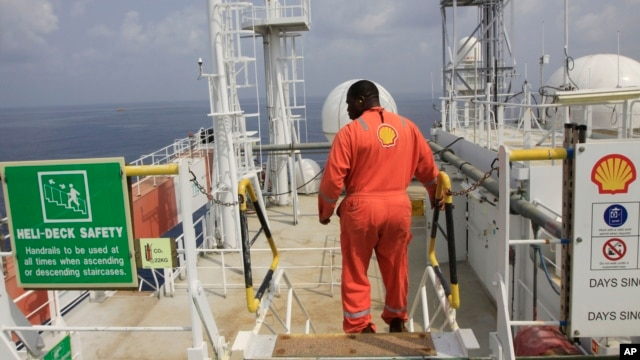 A Shell employee is seen aboard an oil vessel off the coast of Nigeria in this December 26, 2011 file photo.