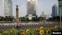 Seorang pengemudi taksi online melewati Bundaran Hotel Indonesia yang kosong saat pemerintah memberlakukan PPKM di Jawa dan Bali. (Foto: Reuters/Willy Kurniawan)