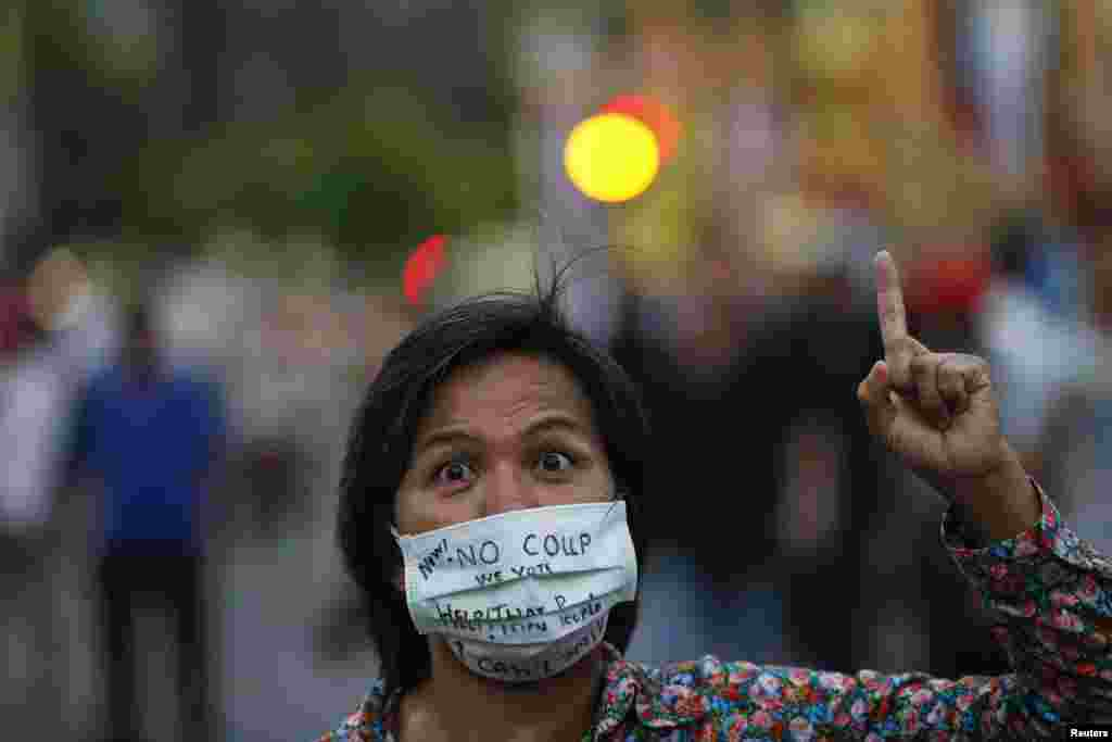 A protester against military rule with messages written on her face mask gestures as protesters gather at the Victory Monument in Bangkok, May 26, 2014.