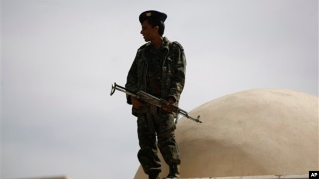 Soldier stands guard outside state security court where suspected al-Qaida militants attend hearing, Sanaa, April 22, 2014.