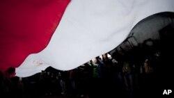 ພວກປະທ້ວງ ພາກັນໂບກທຸງຊາດຜືນໃຫຍ່ຂອງອີຈິບ ທີ່ຈະຕຸລັດ Tahrir ໃນນະຄອນຫຼວງໄຄໂຣ (25 ພະຈິກ 2011)