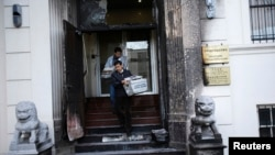 Workers carry stacks of newspaper from the steps of the fire-damaged front of the Chinese consulate in San Francisco, California, Jan. 2, 2014.