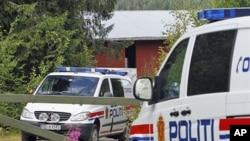图为挪威警车7月28日停泊在嫌犯布雷维克农场前