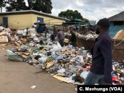 Some Harare citizens walk by a heap of waste which has not been collected for days. Experts say that is a breeding zone for cholera.