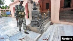 Một nhân viên an ninh Ấn Độ đi bên cạnh các vết chân đẫm máu bên trong ngôi đền Mahabodhi, sau một loạt các vụ nổ tại chùa Bodh Gaya (Bồ Đề Đạo Tràng), ngày 7/7/2013.