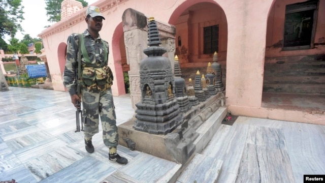 An Indian security personnel walks next to bloody footprints inside the Mahabodhi temple complex, after a series of explosions at Bodh Gaya in the eastern Indian state of Bihar, July 7, 2013.