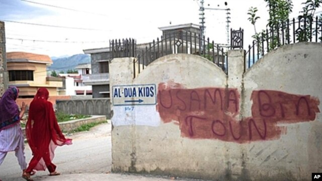 "Pakistani women walk past covered graffiti that reads ""Usama bin Laden toun"" (Osama bin Laden town) in Abbottabad on May 6, 2011, where bin Laden was killed by US commandos in a secret raid on May 2."