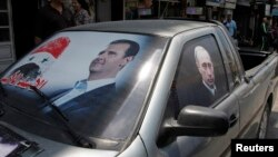 FILE - A poster of Syria's President Bashar al-Assad (L) and a photo of Russian President Vladimir Putin are seen on a car near Latakia, Syria, May 26, 2014.